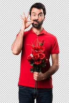 Handsome man holding flowers making silence gesture