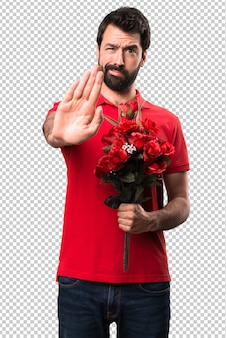 Handsome man holding flowers making stop sign