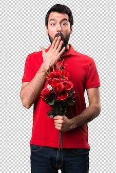 Handsome man holding flowers making surprise gesture
