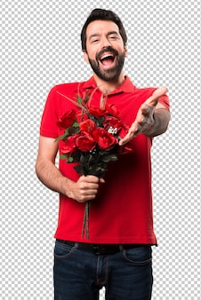 Handsome man holding flowers presenting something