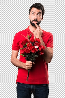 Handsome man holding flowers thinking