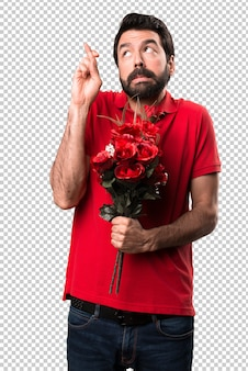 Handsome man holding flowers with his fingers crossing