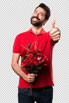 Handsome man holding flowers with thumb up
