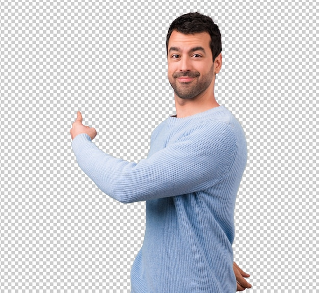 人差し指で後ろを指差しているハンサムな男