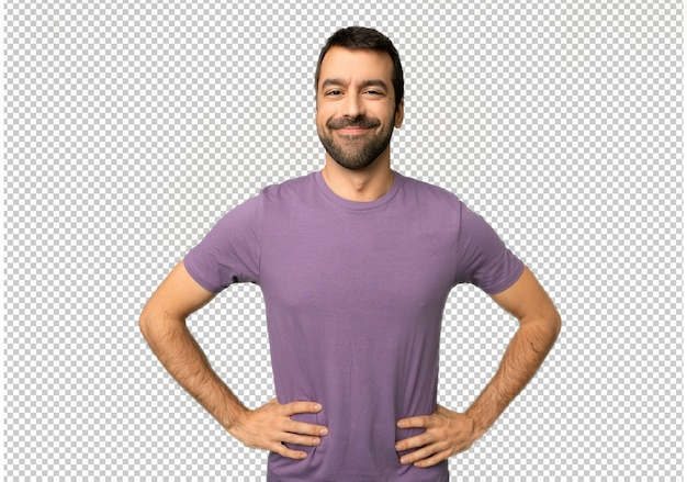 Handsome man posing with arms at hip and laughing looking to the front