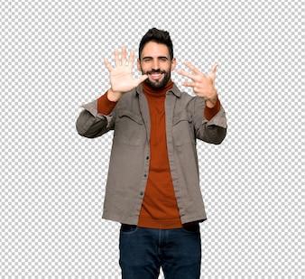 指で9を数えるひげを持つハンサムな男