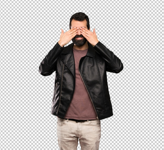 Handsome man with beard covering eyes by hands