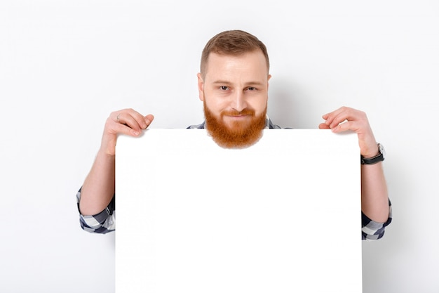 Handsome man with beard holding big white card.