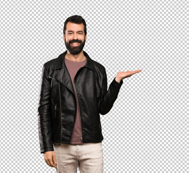 Handsome man with beard holding copyspace imaginary on the palm to insert an ad