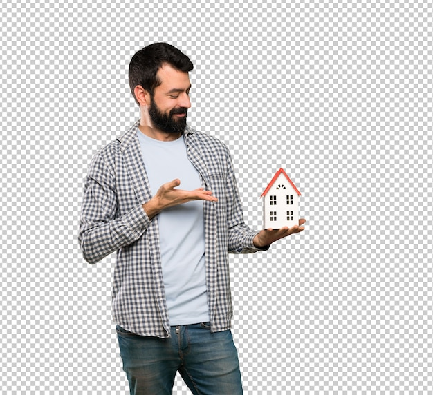 Handsome man with beard holding a little house
