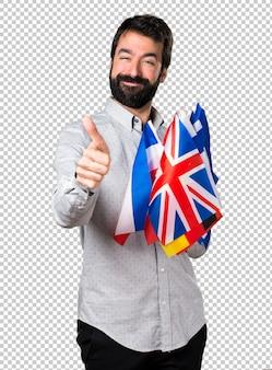 많은 깃발을 들고 수염과 엄지 손가락을 가진 잘 생긴 남자