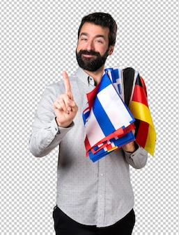 Handsome man with beard holding many flags and counting one