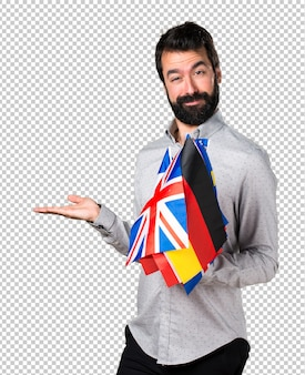 Handsome man with beard holding many flags and holding something