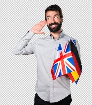 Handsome man with beard holding many flags and listening something