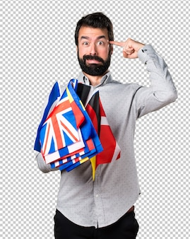 Handsome man with beard holding many flags and making crazy gesture