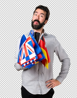 Handsome man with beard holding many flags and making a joke