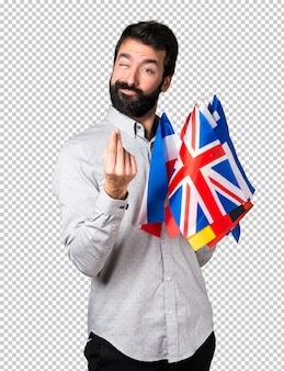Handsome man with beard holding many flags and making money gesture