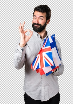 Handsome man with beard holding many flags and making ok sign