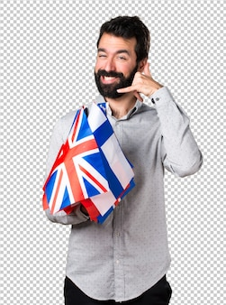 Handsome man with beard holding many flags and making phone gesture