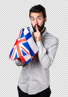 Handsome man with beard holding many flags and making silence gesture