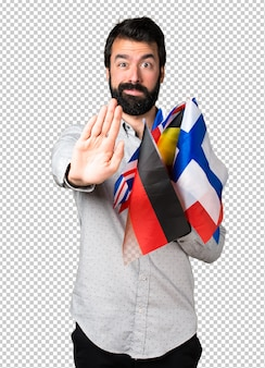 Handsome man with beard holding many flags and making stop sign