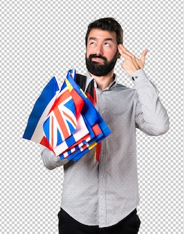 Handsome man with beard holding many flags and making suicide gesture