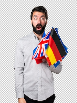 Handsome man with beard holding many flags and making surprise gesture