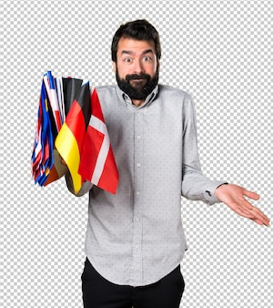 Handsome man with beard holding many flags and making unimportant gesture
