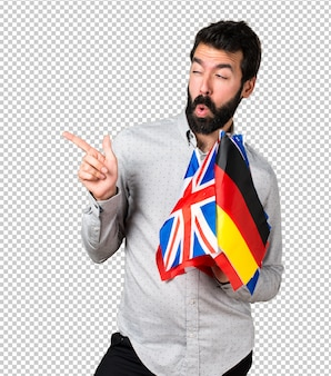 Handsome man with beard holding many flags and pointing to the lateral
