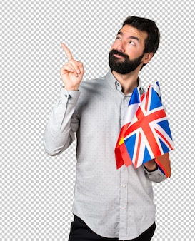 Handsome man with beard holding many flags and pointing up