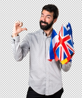 Handsome man with beard holding many flags proud of himself