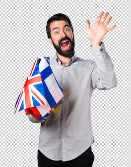 Handsome man with beard holding many flags and saluting