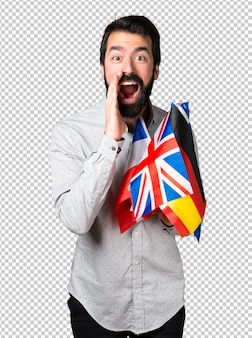 Handsome man with beard holding many flags and shouting