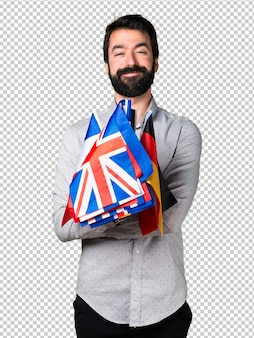 Handsome man with beard holding many flags
