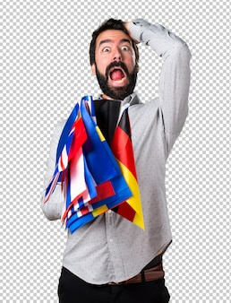 Handsome man with beard holding many flags and