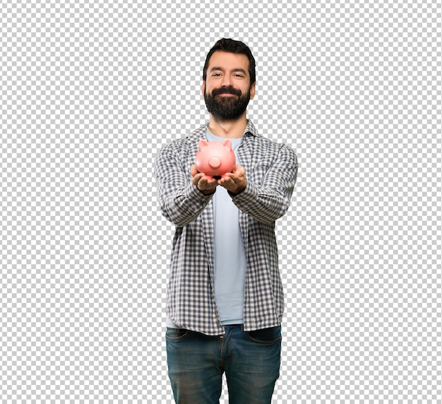 Handsome man with beard holding a piggybank
