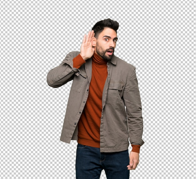 Handsome man with beard listening to something by putting hand on the ear