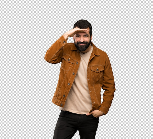 Handsome man with beard looking far away with hand to look something