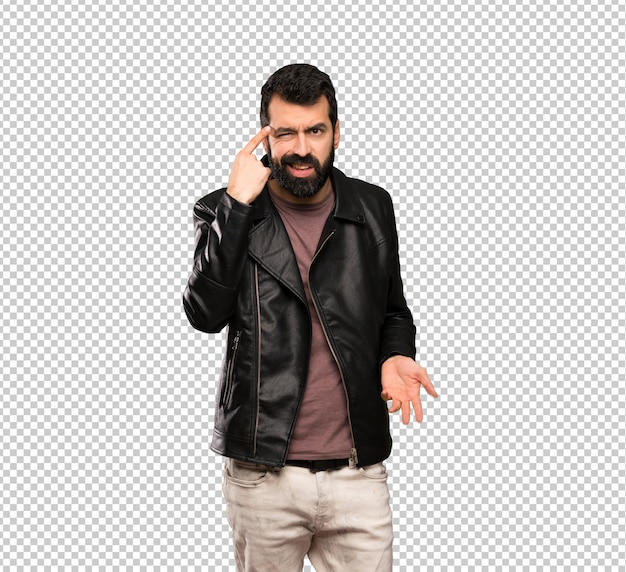 Handsome man with beard making the gesture of madness putting finger on the head