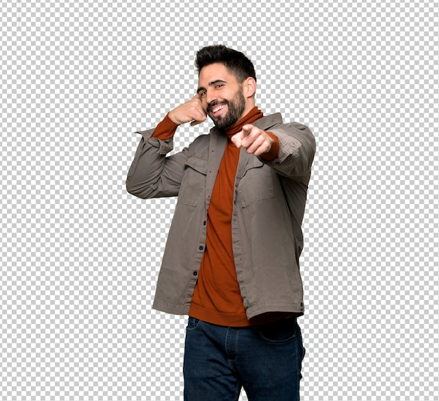 Handsome man with beard making phone gesture and pointing front
