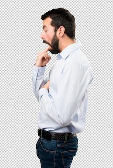 Handsome man with beard making vomiting gesture