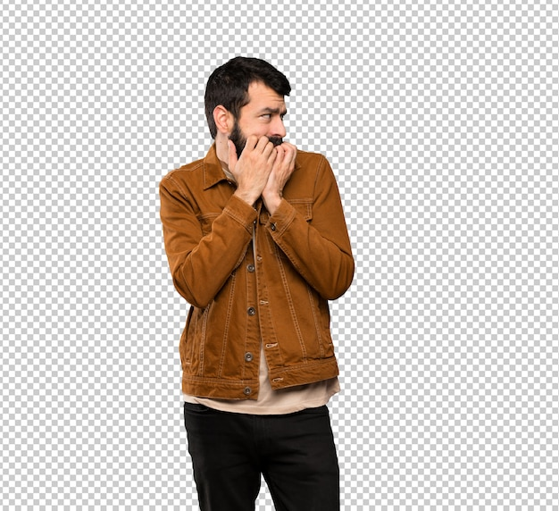 Handsome man with beard nervous and scared putting hands to mouth