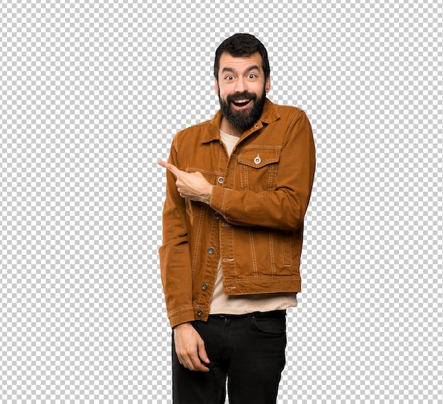 Handsome man with beard surprised and pointing side