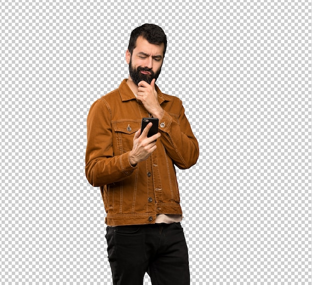 Handsome man with beard thinking and sending a message