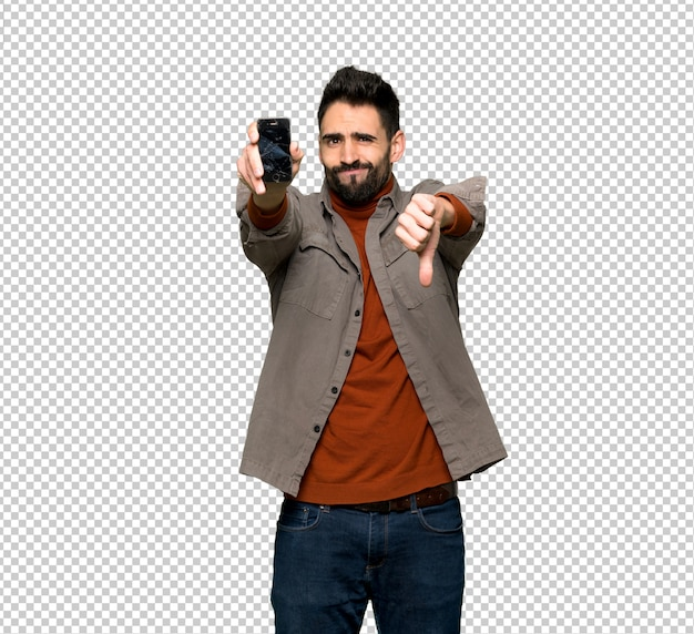 Handsome man with beard with troubled holding broken smartphone
