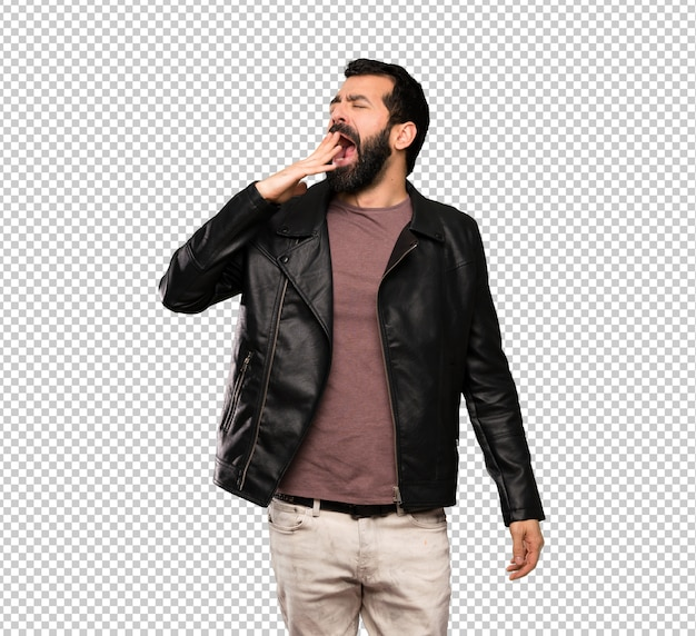 Handsome man with beard yawning and covering wide open mouth with hand