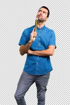 Красивый мужчина в синей рубашке держит большой карандаш