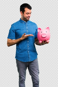 Handsome man with blue shirt holding a piggybank