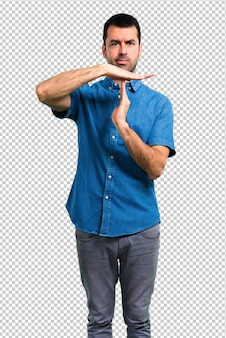 Handsome man with blue shirt making stop gesture with her hand