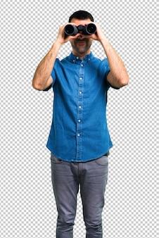 쌍안경으로 파란색 셔츠와 잘 생긴 남자